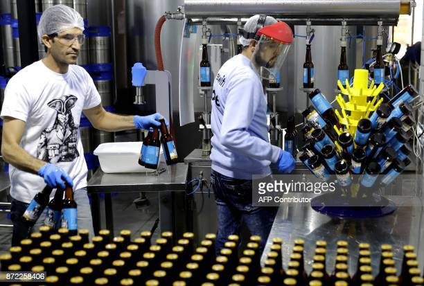 Workers fill beer bottles at the Colonel Beer brewery in the town of Batroun north of Beirut on October 5 2017 For decades beer in Lebanon has meant...