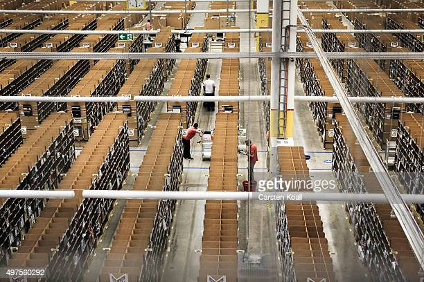 Workers fill inventory among shelves lined with goods at an Amazon warehouse on November 17 2015 in Brieselang Germany Germany is online retailer...