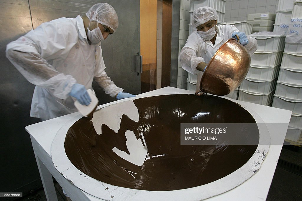 Workers fill, with melted chocolate, a shape for making a ...
