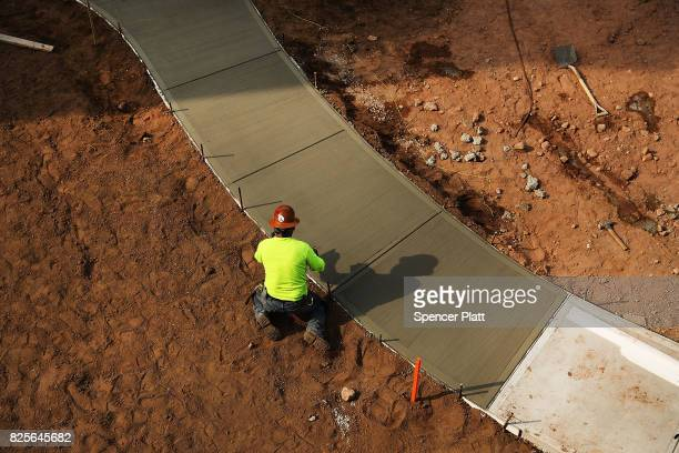 Workers finish a sidewalk at Canal Crossing a new luxury apartment community consisting of 393 rental units near the university city of New Haven on...
