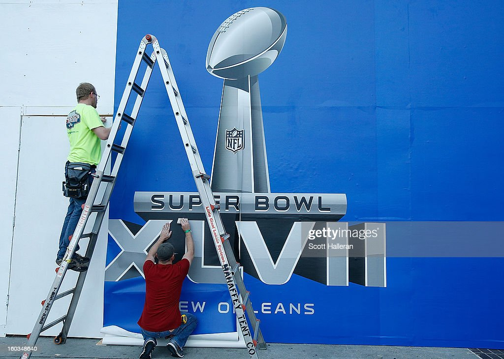 Workers finish a Super Bowl sign prior to the start of Super Bowl XLVII at Mercedes-Benz Superdome on January 29, 2013 in New Orleans, Louisiana.