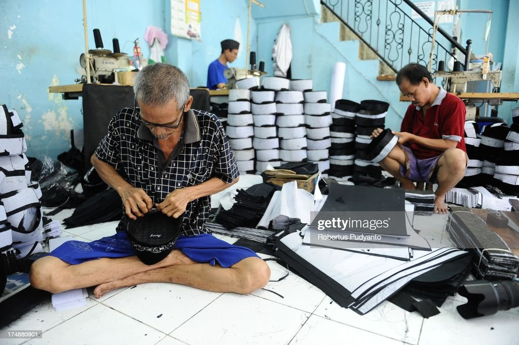 Workers finish attaching the lining of skull caps at Awing traditional Muslim skull cap manufacturers on July 29, 2013 in Gresik, Java, Indonesia. Awing traditional Muslim skull cap manufacturers have received increased demand for their products from Singapore, Malaysia, Brunei Darussalam, as well as domestic buyers, with sales increasing from from 30,000 to 50,000 pieces during the Ramadan period. This skull cap does not crease and has the advantages of good ventilation. The paperless skull cap body is made from high quality velvet material imported from Korea and the United States, with lining materials imported from Japan.
