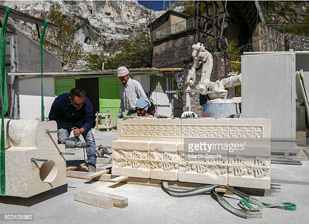 Workers finish one of the marble blocks for the 3D replica of Palmyra's Arch of Triumph at the marble caves of Carrara on April 11 2016 in Carrara...