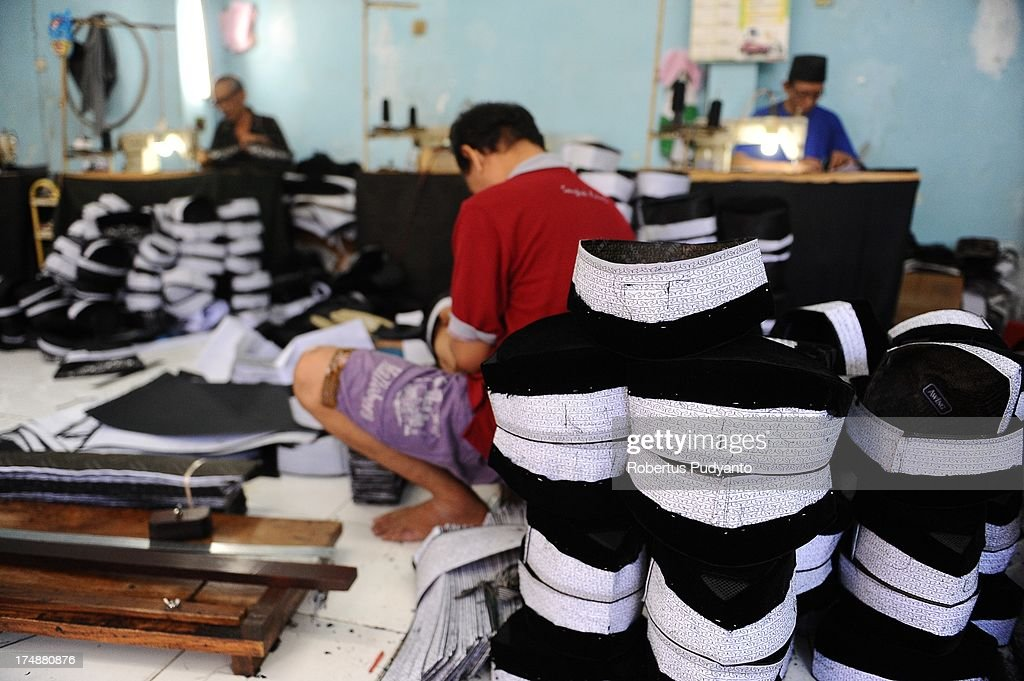 Workers finish sewing the body of skull caps at Awing traditional Muslim skull cap manufacturers on July 29, 2013 in Gresik, Java, Indonesia. Awing traditional Muslim skull cap manufacturers have received increased demand for their products from Singapore, Malaysia, Brunei Darussalam, as well as domestic buyers, with sales increasing from from 30,000 to 50,000 pieces during the Ramadan period. This skull cap does not crease and has the advantages of good ventilation. The paperless skull cap body is made from high quality velvet material imported from Korea and the United States, with lining materials imported from Japan.