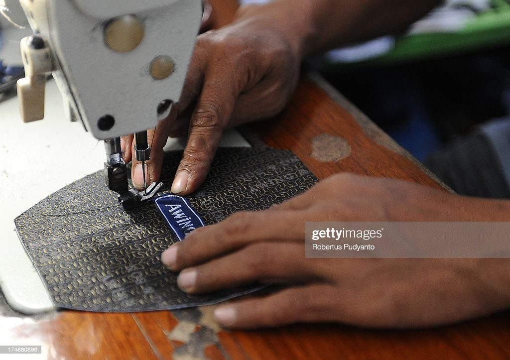 Workers finish sewing the logo of skull caps at Awing traditional Muslim skull cap manufacturers on July 29, 2013 in Gresik, Java, Indonesia. Awing traditional Muslim skull cap manufacturers have received increased demand for their products from Singapore, Malaysia, Brunei Darussalam, as well as domestic buyers, with sales increasing from from 30,000 to 50,000 pieces during the Ramadan period. This skull cap does not crease and has the advantages of good ventilation. The paperless skull cap body is made from high quality velvet material imported from Korea and the United States, with lining materials imported from Japan.