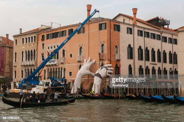 Workers finish to prepare the exhibition 'SUPPORT' by Lorenzo Quinn during the 57th Biennale Arte on May 11 2017 in Venice Italy The 57th...