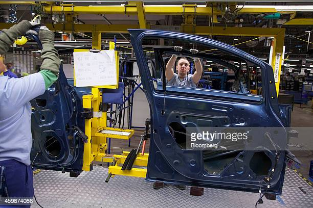 Workers fit rubber trim onto Opel Astra automobile doors on the production line at General Motors Co's Adam Opel AG manufacturing plant in Gliwice...
