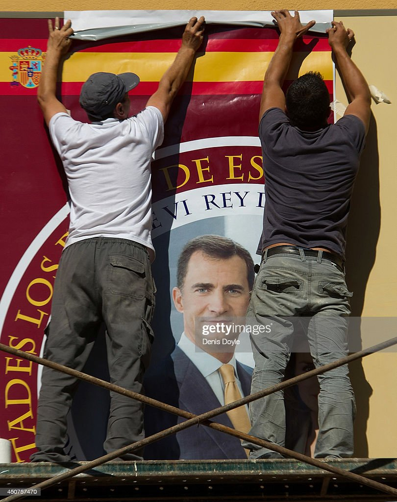 Workers fix a photograph of Prince Felipe to the facade of a souvenir shop near the Royal Palace on June 17, 2014 in Madrid, Spain. Prince Felipe will be crowned <a gi-track='captionPersonalityLinkClicked' href=/galleries/search?phrase=Felipe+VI+of+Spain&family=editorial&specificpeople=4881076 ng-click='$event.stopPropagation()'>Felipe VI of Spain</a> on June 19th after his father King Juan Carlos abdicated on June 2