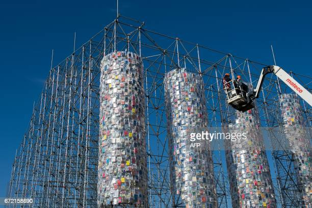 Workers fix books wrapped into plastic bags on a scaffolding as part of the documenta art work 'The Parthenon of Books' by Argentinean artist Marta...