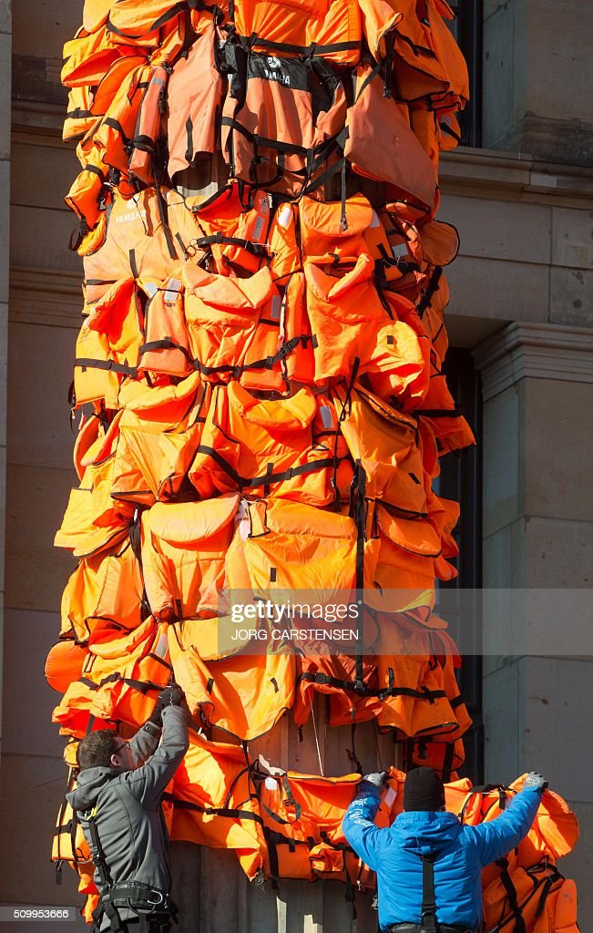 Workers fix life jackets at the columns of the Konzerthaus concert hall at Berlin's Gendarmenmarkt place on February 13, 2016 to complete a temporary installation by Chinese artist Ai Weiwei. Ai Weiwei aims to draw attention to the terrible fate of refugees who were drowned on their way to Europe. The live vests were provided by the Greek island of Lesbos. / AFP / dpa / Jörg Carstensen / Germany OUT / RESTRICTED TO EDITORIAL USE - MANDATORY MENTION OF THE ARTIST UPON PUBLICATION - TO ILLUSTRATE THE EVENT AS SPECIFIED IN THE CAPTION
