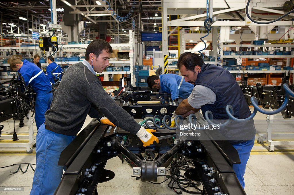 Workers fix parts to the chassis of Ford Cargo trucks on the production line at Ford Otosan, the joint venture between Ford Motor Co.'s Ford Otomotiv Sanayi AS and Koc Holding AS, in Eskisehir, Turkey, on Monday, Nov. 18, 2014. Ford Otomotiv Sanayi AS chief executive officer Haydar Yenigun said in September Turkey is about to 'lose the diamond' which is light commercial vehicle production due to government policies such as tax hikes, ban on their lease, Dunya newspaper says. Photographer: Kerem Uzel/Bloomberg via Getty Images