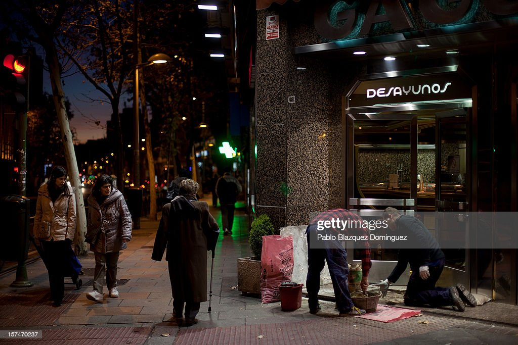 Workers fix the ground of a tapas bar entrance as people walk past on December 3, 2012 in Madrid, Spain. Spain has formally requested 39.5 euro billions bank bail-out of European funds. Economy Ministry of Spain, Luis de Guindos said that 37 euro billions will be paid for the four nationalized banks Bankia, Catalunya Banc, NCG Banco and Banco de Valencia while 2.5 euro billions will be for the 'bad banks'.