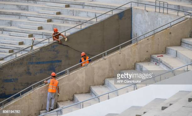 Workers fix the tribunes of the Rostov Arena in the southern Russian city of RostovonDon on August 21 2017 The venue will host five games of the FIFA...