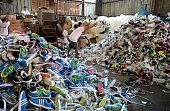 Workers for the Philippine customs bureau pile up thousands of confiscated counterfeit designer footwear products at a custom's warehouse in Manila...