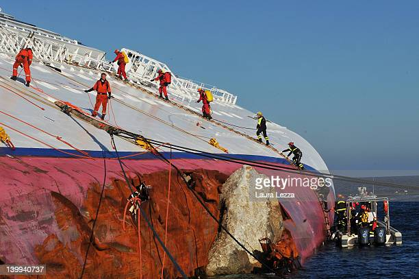 Workers for the Rotterdam based SMIT salvage firm and fire fighters walk up the side of the stricken Costa Concordia as the operation to remove fuel...