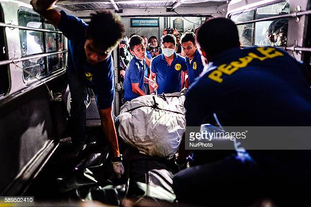Workers from a funeral parlor load into an ambulance a corpse collected from the Paranaque city jail where a grenade blast killed 10 inmates 8 of...