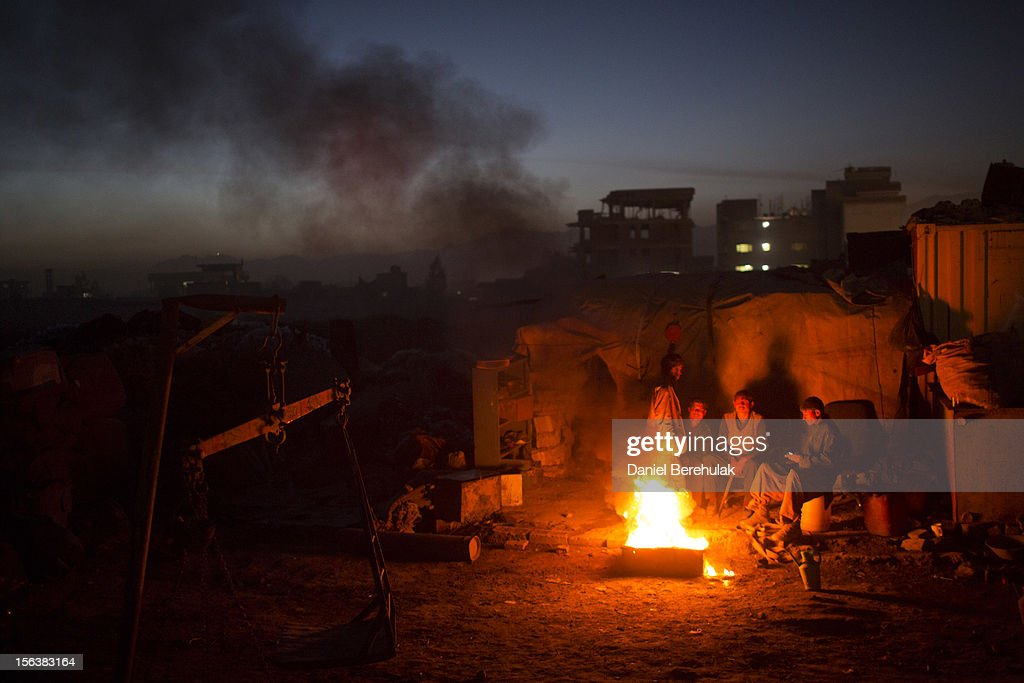 Workers from a scrap yard and Afghan Pashtun boys, who say they were forced from the troubled province of Baglan due to threats from the Taliban, warm themselves by a fire near to a garbage dump site on November 14, 2012 in Kabul, Afghanistan. Children working at the garbage site in Kabul said they can make up to 90 Afghans (USD $1.75) per day collecting cans and other recyclable materials for sale. If they were to stay and work in their home province, with limited options for employment, and join the Police or Army, the Taliban threatened they would come for them and their families, they said.