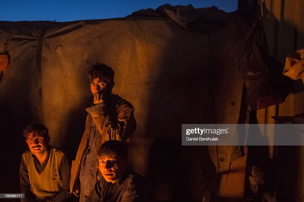 Workers from a scrap-yard and Afghan Pashtun boys, who say they were forced from the troubled province of Baglan due to threats from the Taliban, warm themselves by a fire near to a garbage dump site on November 14, 2012 in Kabul, Afghanistan. Children working at the garbage site in Kabul said they can make up to 90 Afghans (USD $1.75) per day collecting cans and other recyclable materials for sale. If they were to stay and work in their home province, with limited options for employment, and join the Police or Army, the Taliban threatened they would come for them and their families, they said.