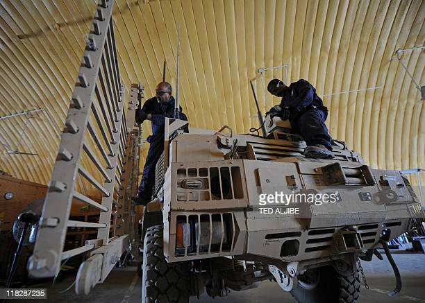 Workers from AC first company a private contractor repair a Mine Resistant ambush Protected vehicle at Camp Clark in Mandozai district Khost province...