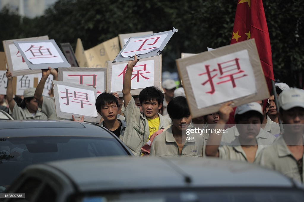 Workers from Japanese company, Meiko Electronics (Wuhan) Limited, march with anti-Japan banners during a protest against Japan's 'nationalizing' of Diaoyu Islands, also called Senkaku in Japan, in Wuhan, central China's Hubei province, on Septermber 18, 2012. Firms ranging from electronics giants Sony and Panasonic to Japan's three big carmakers -- Toyota, Honda and Nissan -- temporarily halted production at some or all of their China-based plants as anger erupted over a disputed island chain claimed by Tokyo and Beijing. CHINA