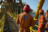 Workers from Oceanografia SA an oil engineering services company stand on a connecting bridge of the Petroleos Mexicanos PolA Platform complex...