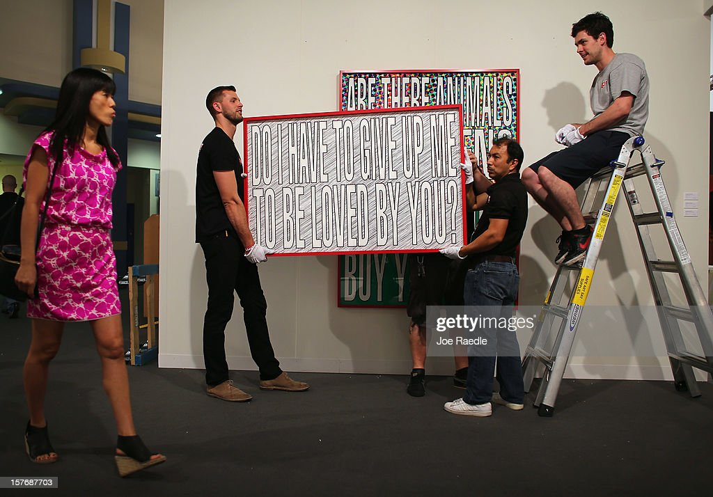 Workers from Safe Art Transport company place a piece of art of the wall of L&M Arts Gallery as Art Basel opens at the Miami Beach Convention Center on December 5, 2012 in Miami Beach, Florida. The 11th edition of the art show runs from December 6 through the 9th.