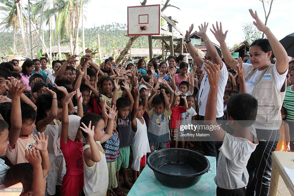 Workers from Spainish based Action Against Hunger teach children how to properly wash their hands in a coastal village devastated by super typhoon Bopha on December 30, 2012 in Lingig, Philippines.