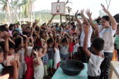 Workers from Spainish based Action Against Hunger teach children how to properly wash their hands in a coastal village devastated by super typhoon...