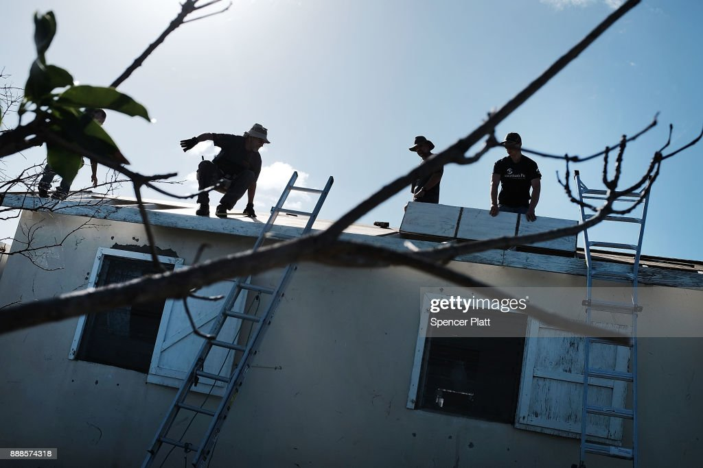 Workers from the charity Samaritan's Purse place a new roof on a home on the nearly destroyed island of Barbuda on December 8, 2017 in Cordington, Barbuda. Barbuda, which covers only 62 square miles, was nearly leveled when Hurricane Irma made landfall with 185mph winds on the night of September six. Only two days later, fearing Barbuda would be hit again by Hurricane Jose, the prime minister ordered an evacuation of all 1,800 residents of the island. Most are now still in shelters scattered around Barbuda's much larger sister island Antigua.