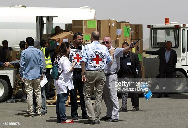 Workers from the International Committee of the Red Cross stand on the tarmac as emergency medical aid from the ICRC is offloaded off a plane...