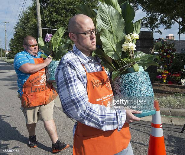 Workers from the local Home Depot hardware store deliver flowers at the gate of WDBJ's television studios August 27 in Roanoke Virginia The former...