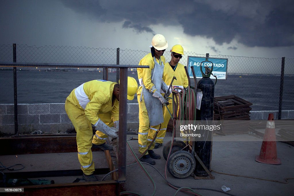 Workers from the Novo Porto Consortium, a group funded by a mix of public and private agencies, gather their equipment as a storm approaches during construction on the Museo do Amanha in downtown Rio de Janeiro, Brazil, on Wednesday, Feb. 26, 2013. The museum will be the centerpiece of the $4 billion Porto Maravilha infrastructure project which aims to revitalize the the city's downtown and port area ahead of Brazil's hosting of the World Cup and Olympic Games. Photographer: Dado Galdieri/Bloomberg via Getty Images