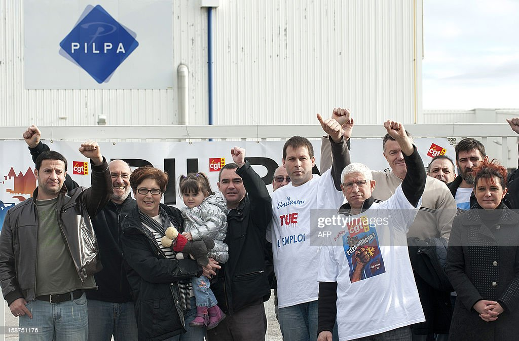Workers from the Pilpa ice cream factory in Carcassonne, southern France, raise their fists as they take part in surveillance rounds to stop the new factory owner from taking or dismantling factory equipment and machines, on December 27, 2012. 112 workers face the threat of being layed-off since July 2012 when the factory's owner sold the site to the R&R ice cream company and have struggled to keep the site and its jobs ever since. As the workers await court rulings pertaining to the factory site and its future, workers say they are being vigilant and have instituted rounds and a night guard to make sure R&R does not leave with the machines and equipment, thereby making it impossible for workers to consider continuing production at the site. AFP PHOTO / REMY GABALDA