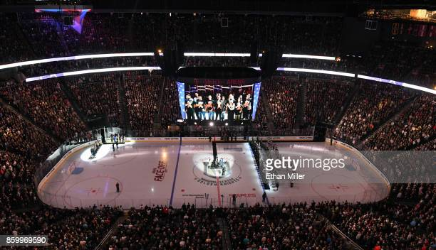 Workers from the Route 91 Harvest country music festival sing the American national anthem before the Vegas Golden Knights' inaugural regularseason...