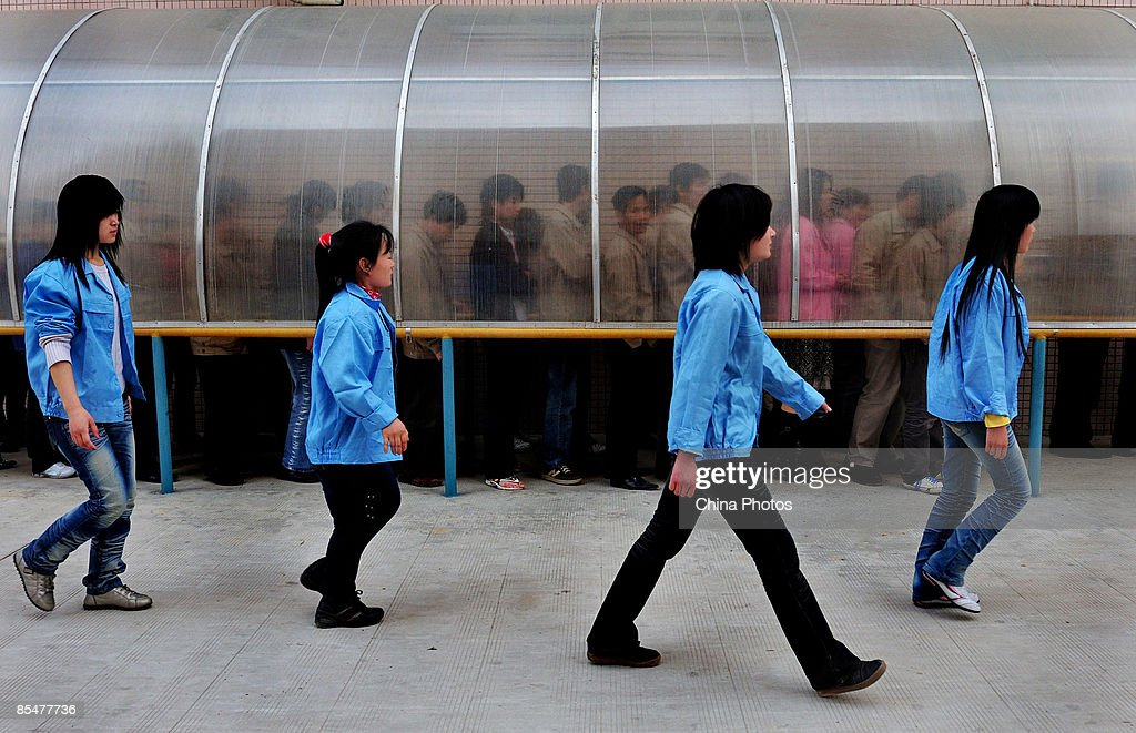Workers from the Shenzhen Quanshun Human Resources Co. Ltd. leave after work at the Pinghu Paper Factory on March 9, 2009 in Shenzhen, Guangdong Province, China. The company, which was established by entrepreneur Zhang Quanshou, supplies workers to enterprises in the Guangdong and Fujian provinces. Since 1997 Zhang has recruited migrant workers and leased them to factories, once the production order of a company is finished workers are then transferred to another one.