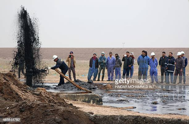 Workers from the South Oil Company watch on as a pipeline ejects oil as the company opens two wells one with the capacity to produce 360000 barrels...