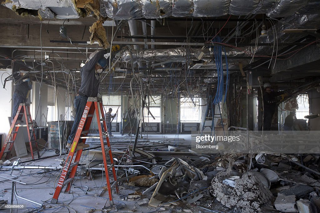 Workers gather debris on the top floor at 75 Rockefeller Plaza during demolition ahead of renovations in New York, U.S., on Monday, Aug. 18, 2014. New landlord RXR Realty Corp. is upgrading the entire 630,000 square feet. The $150 million project includes raising office ceilings from 7.5 feet (2.3 meters) to 9 feet, and relocating mechanical equipment from the top floor to create new high-priced space, said Scott Rechler, RXRís chief executive officer. Photographer: Jin Lee/Bloomberg via Getty Images