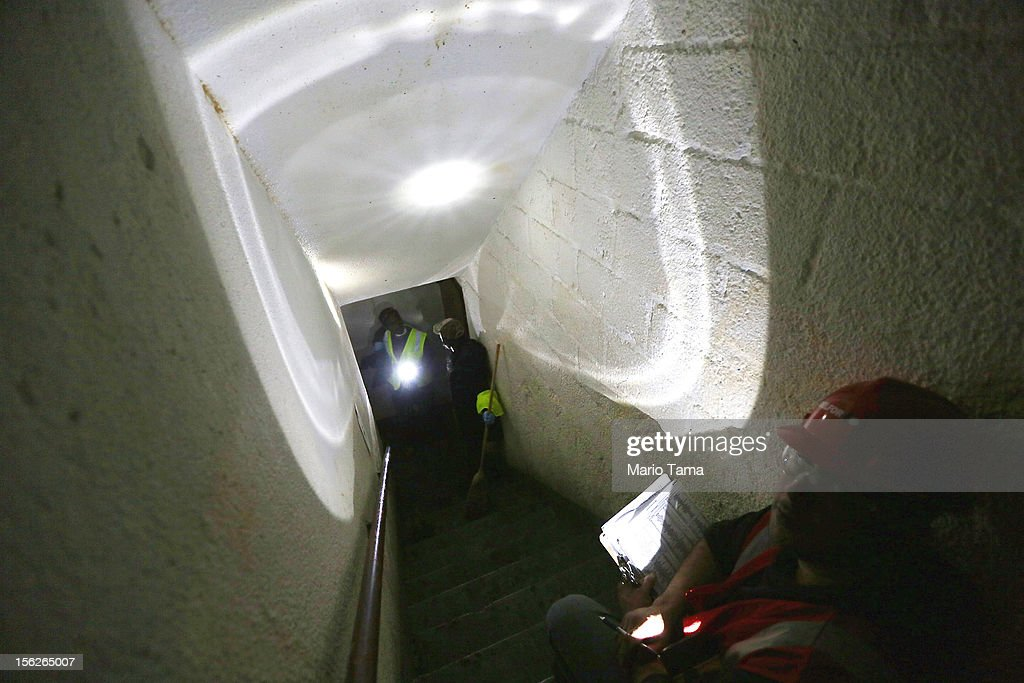 Workers gather in a darkened stairwell in a public housing building that still doesn't have power in the Red Hook neighborhood on November 12, 2012 in the Brooklyn borough of New York City. The neighborhood was hard hit by Superstorm Sandy and some public housing residents remain without power or heat.