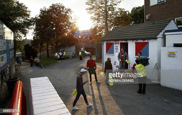 Workers gather outside the club shop before the start of the Vanarama Conference local derby football match between Aldershot and Woking at The...