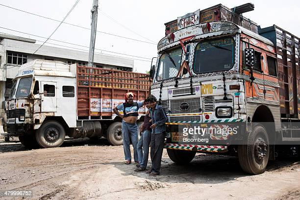 Workers gather round a truck standing idle due to a lack of qualified drivers outside the Caravan Roadways Ltd office at Sanjay Gandhi Transport...
