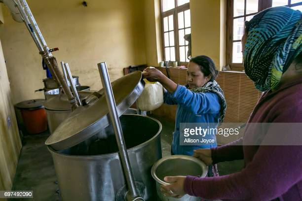 Workers get water from a vat which is powered by solar thermal energy at the Jamyang school which is powered by solar energy on June 12 2017 in Leh...