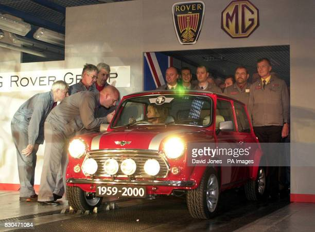 Workers giving advice to singer Lulu as she prepares to drive the 5862nd and final classic Mini off the production line at the MG Rover Group factory...