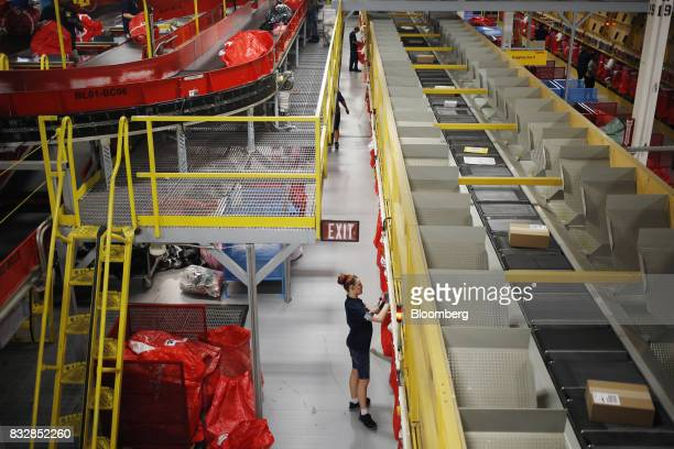 Workers grab bags of sorted packages at the DHL Worldwide Express hub of Cincinnati/Northern Kentucky International Airport in Hebron Kentucky US on...