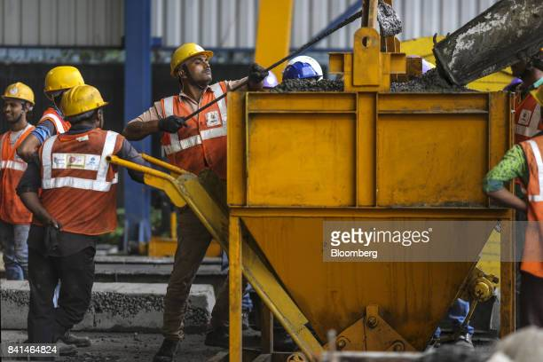 Workers guide concrete from a mixer truck into a kibble at the Mumbai Metro Rail Corp casting yard in Mumbai India on Monday Aug 28 2017 The...