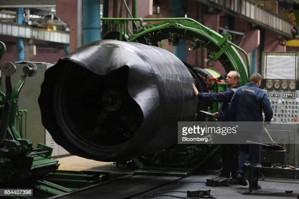Workers guide lengths of rubber onto a machine during the manufacture of a supersized tire at the Belshina JSC tire factory in Babruysk Belarus on...