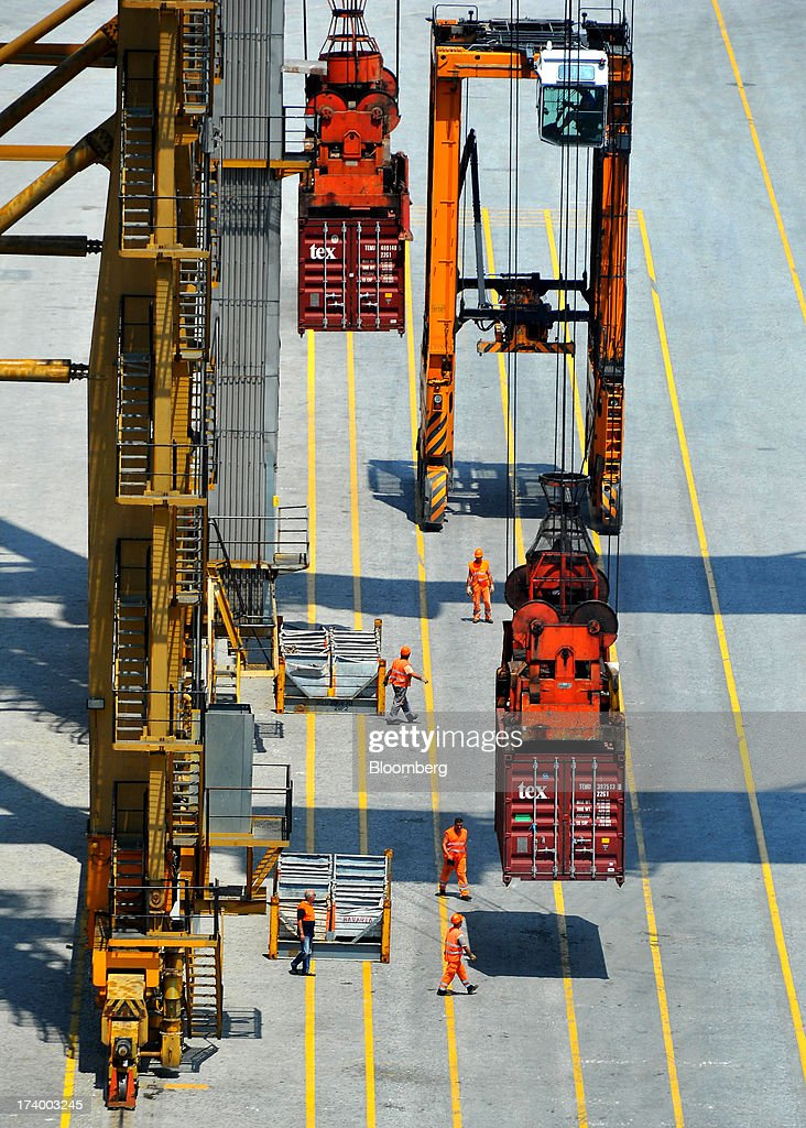 Workers guide shipping containers as they are loaded onto a cargo ship at Thessaloniki Port, operated by Thessaloniki Port Authority SA, in Thessaloniki, Greece, on Thursday, July 18, 2013. Russian Railways is interested in buying Thessaloniki Port and Greek rail operator Trainose SA as one single unit, newspaper Real News reported, citing an interview with the Russian company's CEO Vladimir Yakunin. Photographer: Oliver Bunic/Bloomberg via Getty Images