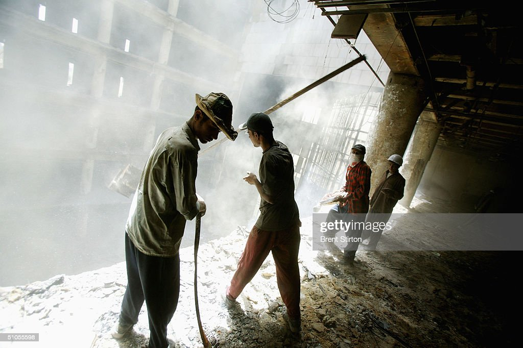Workers gut the Central Bank of Iraq amidst severe asbestos conditions without adequate safety equipment June 2 2004 in Baghdad Iraq The Central Bank...