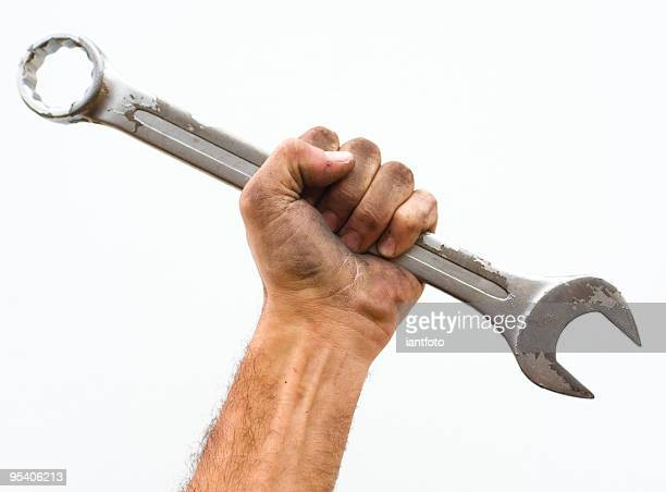 Workers hand and wrench.