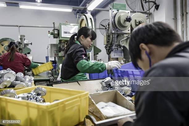 Workers handle drill and sort casters at a factory operated by the Guangdong Shiyi Furniture Co in Foshan China on Tuesday Feb 28 2017 Startup...