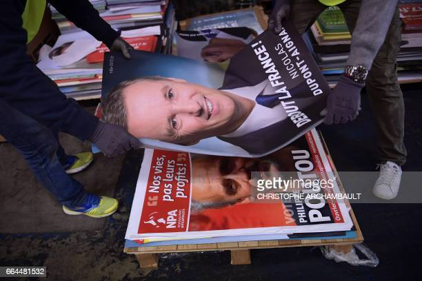 Workers handle election posters of French presidential election candidate for the rightwing Debout la France party Nicolas DupontAignan and French...